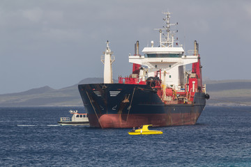 Cargo ship getting in position for making a delivery of industry parts in shallow water on the west coast of the tropical island of Bonaire
