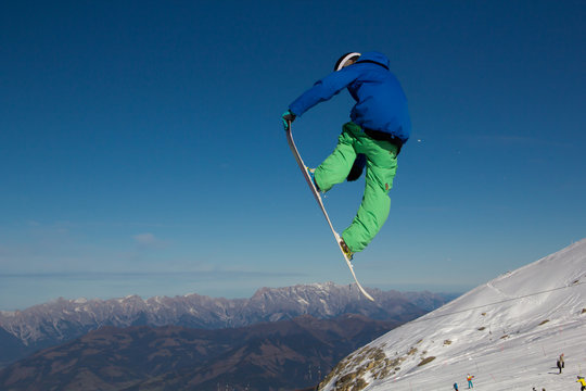 Snowboarder flying high after jumping over a kicker in the Kitzsteinhorn Funpark in the Austrian Alps in Europe performing a tailgrab