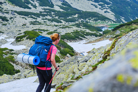Woman with heavy backpack and a rolled sleeping pad, navigating a trekking trail in Retezat mountains (part of Carpathians), Romania, during Summer hiking season, with patches of snow still present.