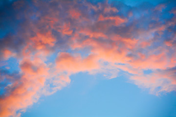 The clouds in the blue sky are illuminated by the orange setting sun. Natural background.