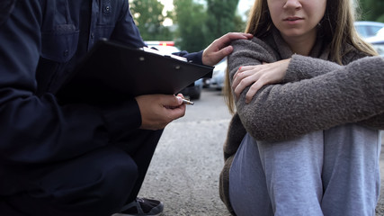 Officer trying to calm down female victim of car accident, shocked girl crying Fototapete