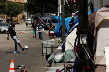 A person kicks a soccer ball as tents and tarps erected by homeless people are shown along sidewalks and streets in the skid row area of downtown Los Angeles, California
