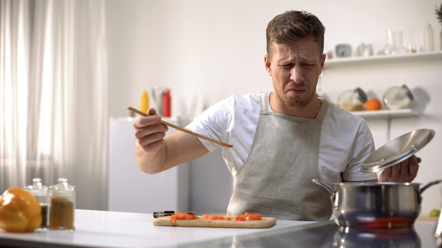 Young man tasting cooked food with disgusted face expression, funny grimacing