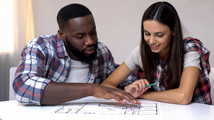 Young mixed-race couple planning interior design of new house, relationship