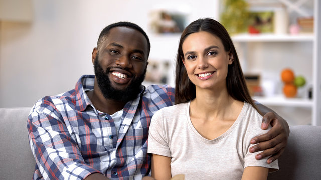 Smiling multiracial couple hugging and looking to camera, social insurance