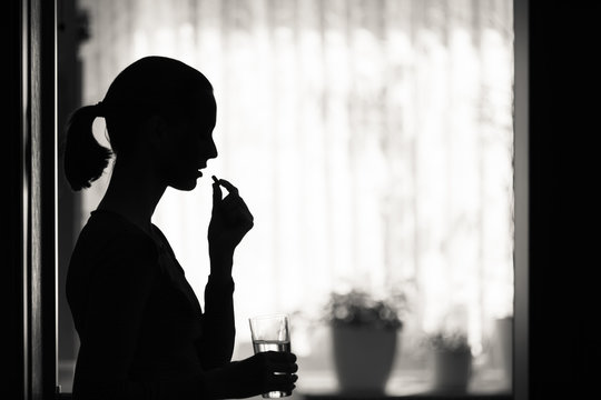 Female taking pill medication in a home setting.
