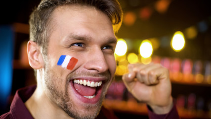 Joyful french fan with painted flag celebrating team victory, making yes gesture