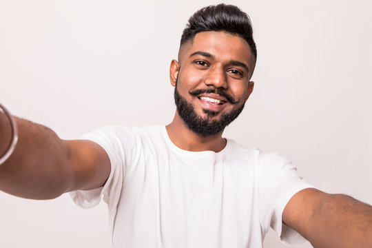 Young pretty indian man taking selfie isolated on white background