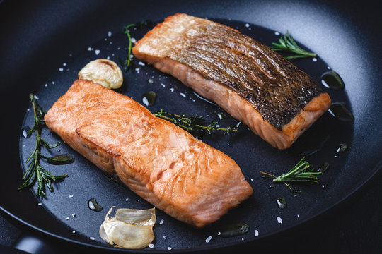 Grilled Salmon Steaks in Frying Pan with Garlic and Rosemary