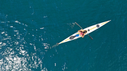 Aerial drone photo of fit man practising sport canoe in calm water sea