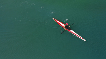 Aerial top view photo of fit athlete practising sport canoe in tropical exotic Caribbean destination with emerald calm sea