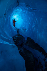 Fototapete - Ice climber with long axe admiring narrow section of ice deep in a dark ice cave. Light shines through the ceiling to illuminate the climber.