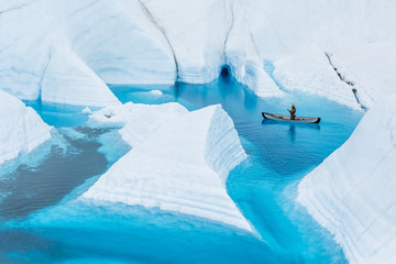Wall Mural - Ice climber canoeing narrow canyons and fins that look like icebergs in front of an ice cave in Alaska.