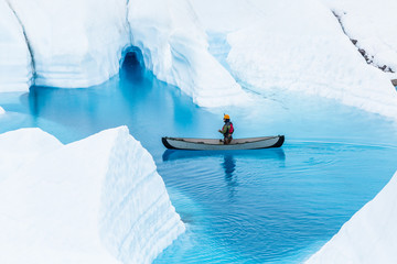 Wall Mural - Canoe in front of a small ice cave in the rain. Boating on a glacier lake in remote Alaska.