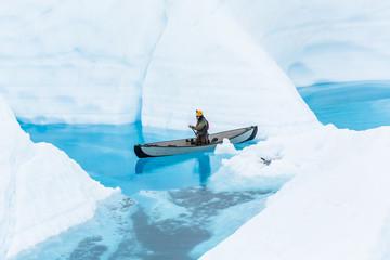 Wall Mural - Ice climbing guide on the Matanuska Glacier paddling a canoe through narrow flooded canyons of a glacier lake.