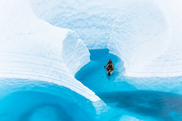 Wall Mural - Canyoneering in a boat on a glacier, a young man paddles through a narrow section of blue water surrounded by walls of ice.