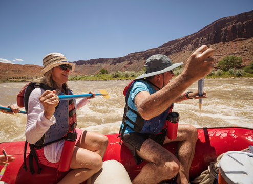 Baby Boomer couple enjoying sunny day river rafting in Moab, Utah