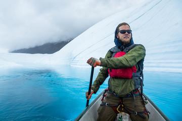 Wall Mural - Man paddling canoe on wide open glacier lake of deep blue color on top of the Matanuska Glacier in Alaska