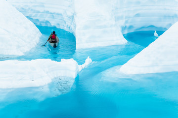 Wall Mural - Exploring a melting glacier by canoe, a young man paddles into a canyon flooded by warming temperatures.