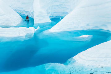 Wall Mural - Ice climber boating through winding canyons flooded by glacier water of the Matanuska Glacier in the Alaskan wilderness.