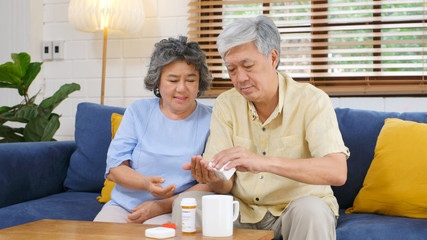 Senior asian couple take pill medicine for elderly healthy lifestyle while sitting on sofa at home living room, retirement people routine, medication and health care concept