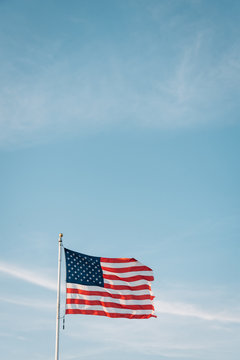 An American flag flying with a blue sky