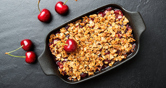 Cherry crumble in black baking dish on black stone background.