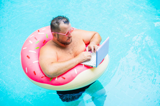 serious Funny fat male in pink glasses on an inflatable circle in the pool works on a laptop portraying a girl.