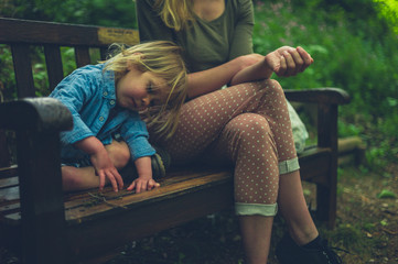 Mother and toddler sitting on bench in the woods