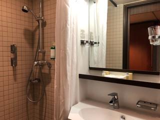 Altmodisches Badezimmer auf Kreuzfahrtschiff mit gekachelter Dusche und Waschtisch mit Spiegel und...