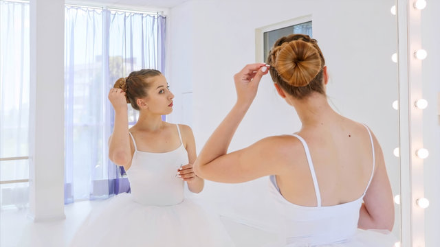 Ballerina in white tutu does her hair standing in front of the mirror in theatre dance class. She fixes the hair pulled into a bun with bobby pins. Portrait shot in mirror reflection.