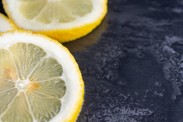 Close-up on top view of slices of lemon on wet black stone background in horizontal with copy space