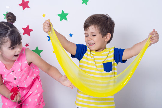 Kid playing hand made toy called slime. Children play with big yellow slime. Kid squeeze and stretching slime.