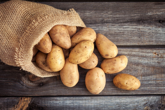Raw potato food . Fresh potatoes in an old sack on wooden background