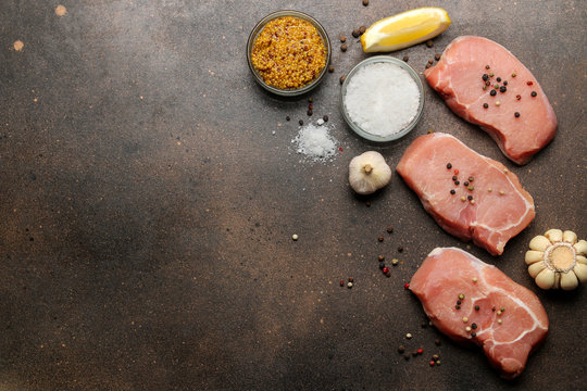 Raw pork steak, meat and ingredients for cooking, spices, herbs and vegetables on a dark background. top view. space for text