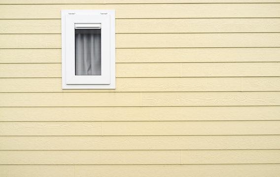 Fenster in gelber Bretterwand