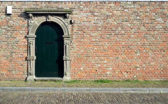 Alte Rundbogentür in rustikaler Ziegelwand