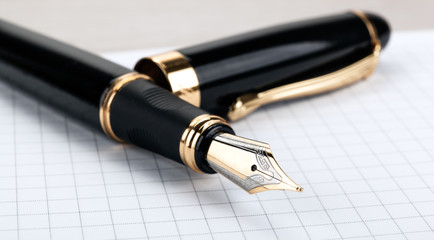 golden fountain pen on the notepad on a table
