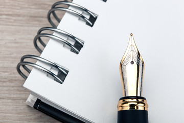 fountain pen on the notepad on a wooden table