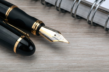 golden fountain pen near the notepad on a wooden table