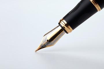golden fountain pen writes on a white background