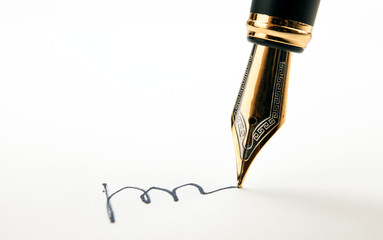 golden fountain pen leaves a signature on a white paper