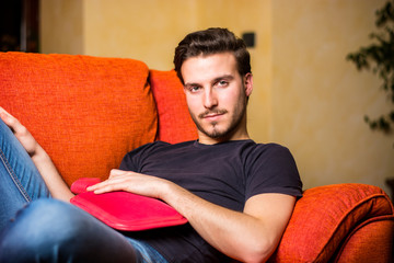 Young man with hot water bottle on stomach, resting on couch at home