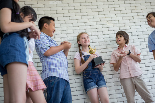 girl holding trophy cup with group Cute Children student clapping hands celebrating together  in classroom at school . kid . child  . Early education .multiethnic