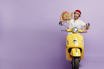Happy male courier rides motorbike, keeps pile of boxes with delicious pizza, delivers to people and does his duties during work, isolated on purple wall, free space on left. Fast delivery concept