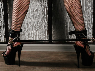 BDSM outfit for adult sex games. Women's legs in black stockings in a mesh in high heels are shackled with shackles and bandage