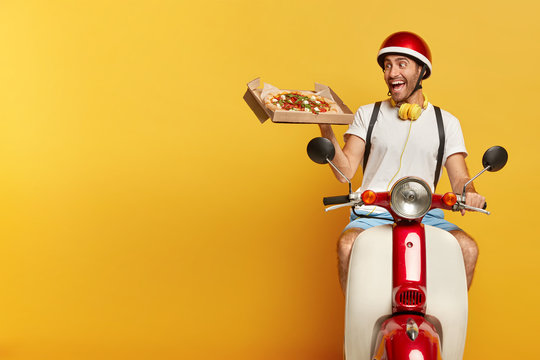 Responsible pizza delivery guy looks with overjoyed face expression at tasty snack, wants to eat, works in pizzeria, maintains good service, uses motorbike for transportation food to clients