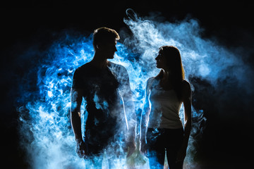 The man and woman standing near the smoke in the dark