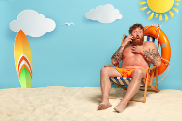 Shot of astonished bearded guy has red sunburned skin, talks on smartphone, hears shocking news from interlocutor, enjoys recreation time, sits at beach, has good rest near sea. Summer travel concept