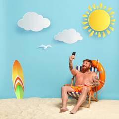 Happy shirtless ginger man makes selfie on beach chair, shares pics with friends online, rests in paradise place with bright yellow sun, white sand and blue sea. Summer time and lifestyle concept